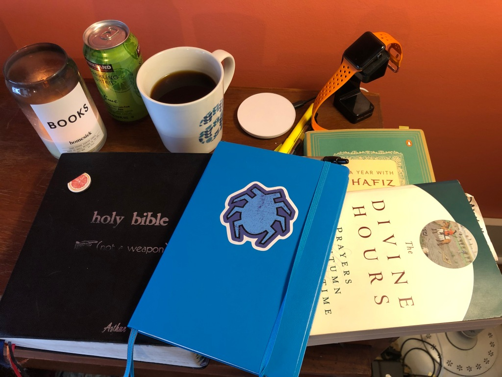 A picture of a lit candle, full coffee cup, assorted chargers, a smart watch, and four books: A Holy Bible, A Year with Hafiz, The Divine Hours, and a blue journal with a beetle sticker on nit.